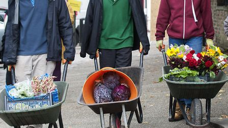 Harington Scheme students barrow produce up Highgate High Street to sell on stall in Pond Square. Pi