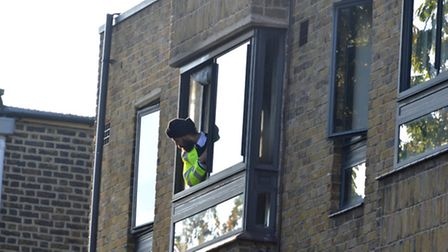 A police officer looks out of a window at the rear of Ashton Court, Camden Road, following a fire at