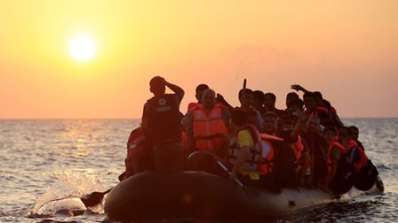 Refugees paddling a rubber dinghy close to the beach near Kos. Photo: PA