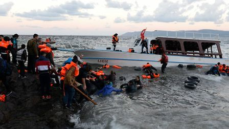 Refugees from the capsized boat are pulled to shore. Picture: Doug Kuntz