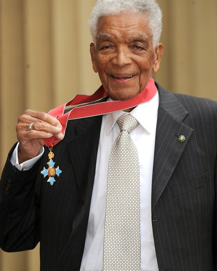 Actor Earl Cameron poses outside Buckingham Palace with his CBE, presented by the Prince of Wales, L