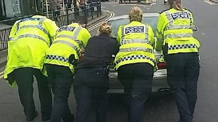 Police officers pushed the car to safety (Picture: Metropolitan Police)