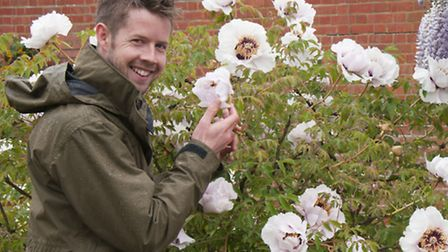Matthew Pottage as he collects material for a hand tried posy, at RHS Garden Wisley. PA Photo/RHS/Ti