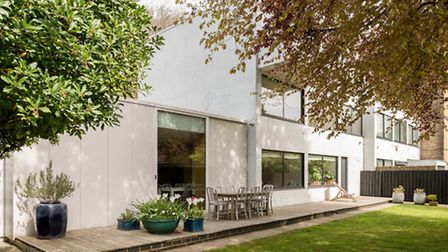 The ground floor features a full-width deck and a garden with mature trees