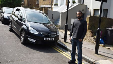 Mr Khan's son Danny Khan with the offending double yellow lines in Brookfield Road (Picture: Ken Mea