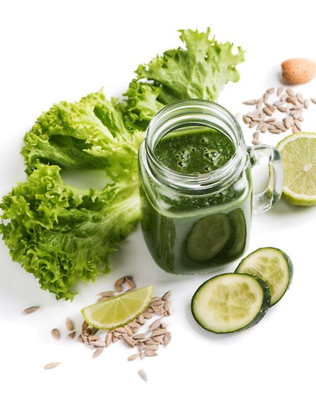 Smoothie of green vegetables ( leafy kale and cucumber) with lime and seeds of sunflower isolated o