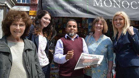 Nurul Islam celebrates at his Belsize Park kiosk with customers and Ham&High reporter Emily Banks, r