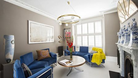 Blue velvet sofas in the living room are a bright counterpart to the chic grey walls