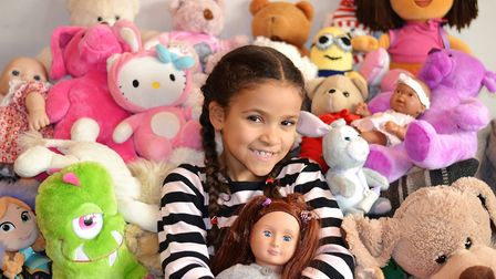 Amber surrounded by cuddly toys helping the Barnardo's Christmas appeal. Picture: Barnardo's.