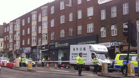 Police at the scene of a crash between a motorcycle and a van in Finchley Road this morning