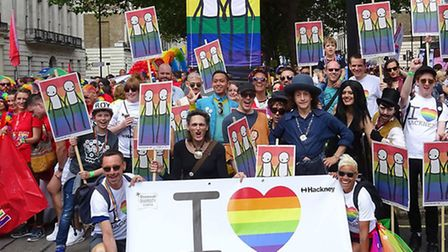 People marching at Pride in London, with the banner created by street artist Stik