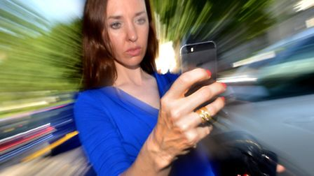 Emma Bartholomew doing exactly what you shouldn't - walking down the street with her phone on show w