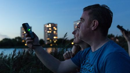 A bat walk on the Woodberry Wetlands, with participants using ultrasound bat detectors to hear the n