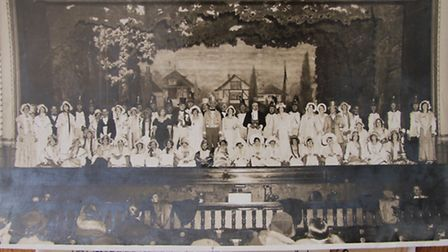 The full cast of the Alexandra Palace Operatic and Dramatic Society on the stage of the Alexandra Pa