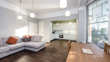 Large windows flood the living room of the Fitzjohn's Avenue one-bed with light