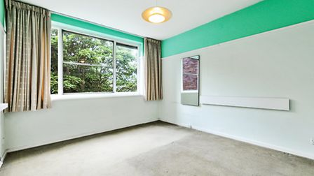 The three-bedroom flat in this 1970s block has large, light rooms that will benefit from an update