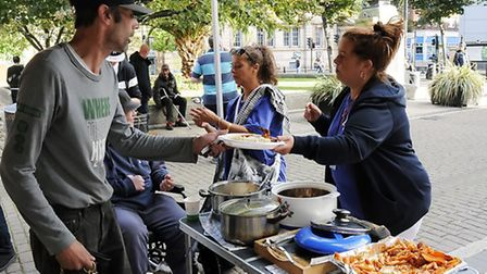 Donna Farrugia hands a hot meal to homeless man Andy Hutchinson at the Dee Dee Help the Homeless pro