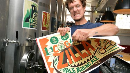 Peter Holt owner of Howling Hops brewery in Queen's Yard E9 rips the Cog-Zilla brew poster.
