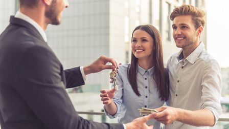 Handsome young businessman is giving keys to happy smiling young couple. Young man is giving money.
