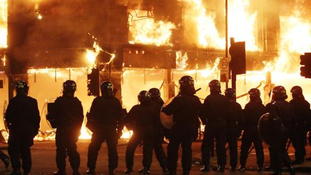 Riot police stand in line as fire rages through a building in Tottenham, north London as trouble fla