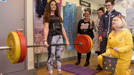 Bethany Wylie from Specsavers in Lowestoft lifts 100kg as part of the stores fundraising event for t