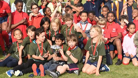 The Gospel Oak team (in green) show off their trophy after beating St Aloyius' (in red) in the A fin