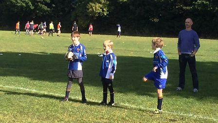 Three youngsters stand on the line in readiness for a drill while a practice match takes place in th