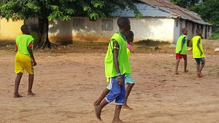 Children play barefoot but wearing bibs, supplied by Priory Park, in Ziguinchor
