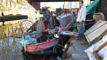 Jahne Cleaver and Dylan Stockli with their leaking listing barge on the canal in Hackney
