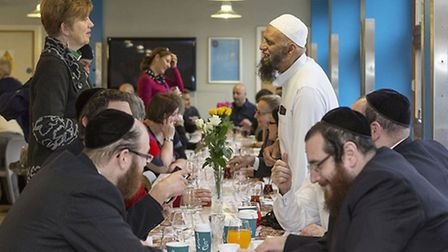 Representatives from different religious groups share bread at the community breakfast