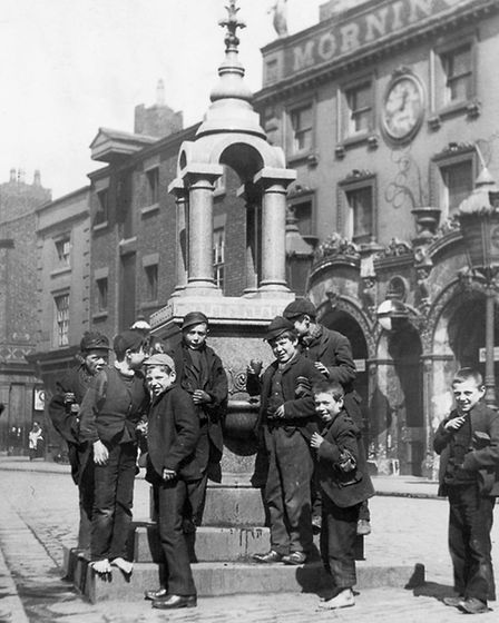 circa 1895:Young shoe-blacks take some time off at the water fountain opposite the 'Morning Star' pu