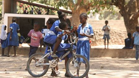 Youngsters in the Gambia with a bike shipped out by Hackney cadets.