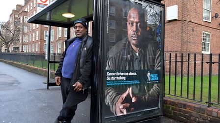 Errol McKellar stands next to his photo, which appears on an awareness advertisment for Prostate Can
