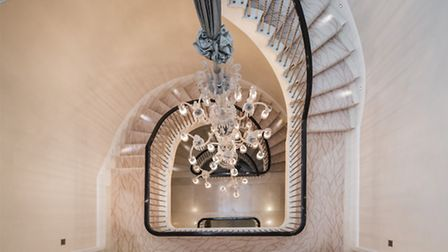 A huge chandelier trails down the sweeping helical staircase