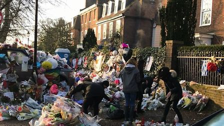 Friends gather outside his Highgate home to sort the sea of flowers and tributes to create a garden