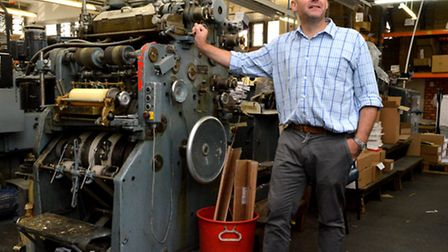 Baddeley Brothers Ltd Hackney. Chris Pertwee stands next to one of the machines in the print room