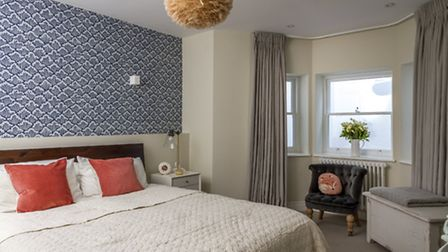 An accent wall of eye catching wallpaper brings colour and texture to the master bedroom