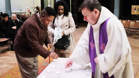 Joseph Burke-Monerville's parents light a candle at a memorial service at St-John-at-Hackney Church,