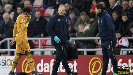 Danny Rose (left) limps off to join manager Mauricio Pochettino (right) on the touchline during Tues