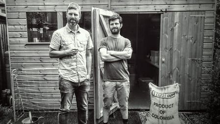 Neil and Ricardo outside the garden shed they used to roast the coffee in