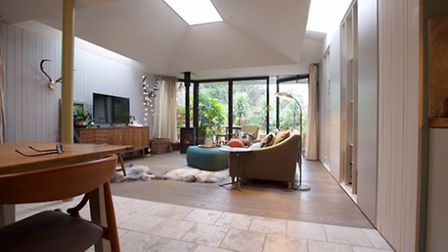 Natural stone and timber flooring defines the living and dining areas in the main reception room