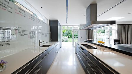 The clients discovered that the glass splashback doubled nicely as a family planner