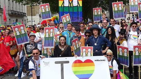 People marching at Gay Pride, with the banner created by street artist Stik