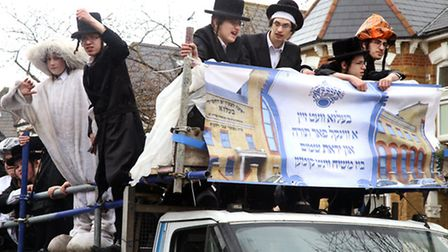 Boys standing in the back of an open truck driving down Fairholt Road, during the Jewish holiday Pur