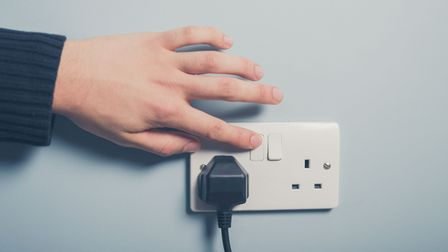 A man turning on an electrical appliance at the socket