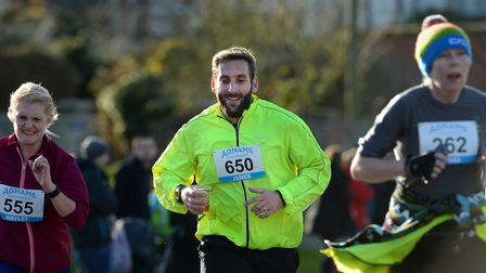 One competitor, Jame, clutches his plastic glass of beer as he nears the finish of the Adnams 10k in