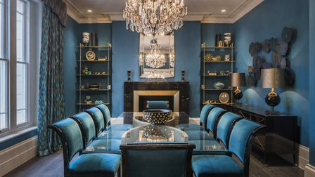 The royal blue dining room has a hint of Lord Sugar's board room about it