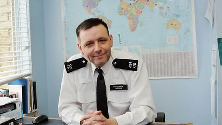 Pc Neil Parham in his cabin. Behind him is a world map he uses to mark global news. Photo: Dieter P