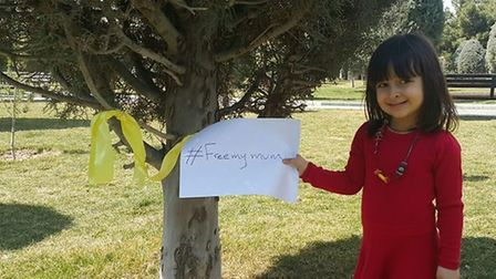 Gabriella ties a yellow ribbon on a tree for her mum