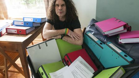 Mark Clewes with his huge stack of documents. Picture: Nigel Sutton